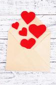 Vackra gamla kuvert med dekorativa hjärtan på trä bakgrund — Stockfoto