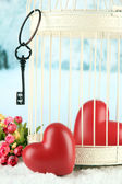 Hearts in decorative cage on winter background — Stock Photo