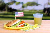 Tasty sandwich with cutlet on color plastic plate on bright background — Stock Photo