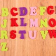 Stock Photo: English alphabet on wooden background