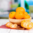Ripe sweet tangerines with spices in bowl, on napkin, on bright background — Stock Photo