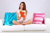 Piękna młoda kobieta siedzi na kanapie z karty na szarym tle — Zdjęcie stockowe