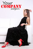Beautiful young woman in black dress on sofa on white background — Stock Photo