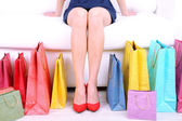 Female in red shoes sitting on sofa with shopping bags close up — Foto de Stock