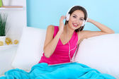 Beautiful young woman listening music on sofa on blue background — Stock Photo