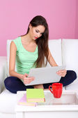 Beautiful young woman sitting on sofa with laptop on pink background — Foto de Stock