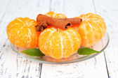 Ripe sweet tangerines with spices on color plate, on wooden background — Stock Photo