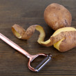 Peeler and fresh potato on wooden background — Stock Photo