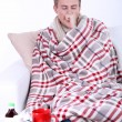 Stock Photo: Guy wrapped in plaid sitting on sofis ill