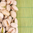 Pistachio nuts on bamboo background — Stock Photo