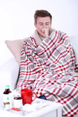 Guy wrapped in plaid sitting on sofa is ill — Stock Photo