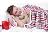Guy wrapped in plaid lies on sofa is ill — Stock Photo