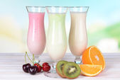 Milk shakes with fruits on table on light blue background — Stock Photo