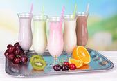 Melk schudt met vruchten op tafel op lichte blauwe achtergrond — Stockfoto