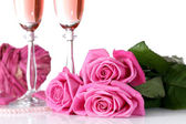 Composition with pink sparkle wine in glasses, and pink roses isolated on white — Stockfoto