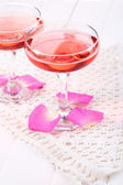 Composition with pink sparkle wine in glasses and rose petals isolated on white — Stock Photo