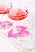 Composición con brillo rosa vino en copas y pétalos de rosa aislados en blanco — Foto de Stock