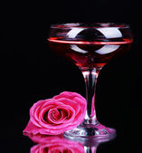 Composition with pink sparkle wine in glass and rose isolated on black — ストック写真