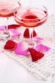 Composition with pink sparkle wine in glasses and rose petals isolated on white — Zdjęcie stockowe
