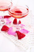 Composition with pink sparkle wine in glasses and rose petals isolated on white — Foto Stock