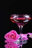 Composition with pink sparkle wine in glass and rose isolated on black — Stok fotoğraf