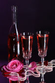 Composition with pink wine in glasses, bottle and roses on dark color background — Foto Stock