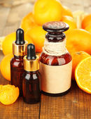 Tangerine essential oil and tangerines on wooden table — Stock Photo
