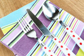 Kitchen cutlery on napkin on wooden table — Stock Photo