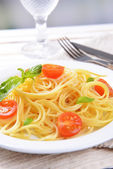 Delicious spaghetti with tomatoes on plate on table close-up — Stock Photo