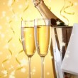 Champagne bottle in bucket with ice and glasses, on yellow background with lights — Stock Photo #39804165