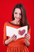 Attraktiv kvinna med vykort, på röd bakgrund — Stockfoto