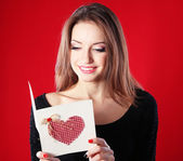 Attractive woman with postcard, on red background — ストック写真
