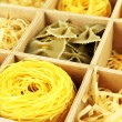 Nine types of pasta in wooden box sections close-up — Stock Photo #39935637