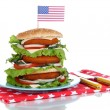 Composition with huge burger on color plate and USA flag, isolated on white — Stock Photo #39936227