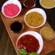 Various sauces on chopping board on table close-up — Stockfoto #39936759