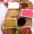 Various sauces on chopping board on table close-up — Stockfoto