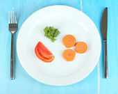 Small portion of food on big plate on wooden table close-up — Stock Photo