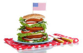 Composition with huge burger on color plate and USA flag, isolated on white — Zdjęcie stockowe