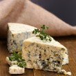 Tasty blue cheese with thyme, on wooden table, on grey background — Stock Photo #39948583