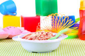 Bowl of porridge for baby on toys background — Stock Photo