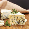 Tasty blue cheese with thyme, on wooden table, on grey background — Stock Photo #39959365