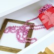 Gift box and beads in open desk drawer close up — Stock Photo #39959773