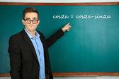 Young teacher near chalkboard in school classroom — Foto Stock