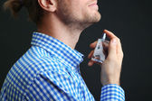 Handsome young man using perfume on black background — Stock Photo