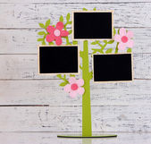 Holder in form of tree with instant photo cards on color wooden background — Stock Photo