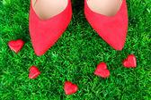 Mooie rode vrouwelijke schoenen, op groen gras achtergrond — Stockfoto