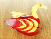Carving fruit pattern of swan on wooden table — Stock Photo