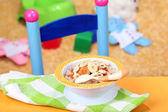 Bowl of porridge for baby and toys on table, on toys background — Stock Photo