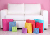 Colorful shopping bags on sofa, on color wall background — Stock Photo
