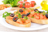 Delicious bruschetta with tomatoes on plate on table close-up — Stock Photo